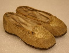 """Pair of child's shoes. Leather soles. Exterior gold brocade silk. Slip on shoe - no straps or ties. Lined with plain linen. Leather insert on interior. Trim sewn around edge of opening of shoe in plain gold silk. ca. 1880-1890 5 3/4"""" long x 1 1/2"""" high x 2"""" wide"""
