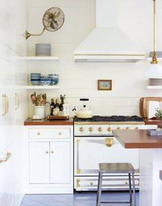 white kitchen/range with brass details