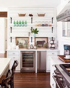 White kitchen with wood floor, board walls, and open shelves on wrought iron brackets.