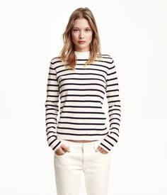 Fine-knit cotton sweater with long sleeves, buttons on one shoulder, and mock turtleneck collar.