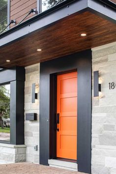 The contrasting vertical orange front door and wide black surround draw the eye in and create a welcoming entry. The accessories were also not overlooked – the sleek sconces, slim mailbox, and address numbers complete the finished look. Modern Entrance Door, Modern Exterior Doors, Modern Front Door, Exterior Front Doors, House Paint Exterior, House Entrance, Exterior Design, Bright Front Doors, Orange Front Doors