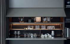 Detail of the flap open units with built-in led lamps. Inner shelf and partition element carbone mat lacquered.
