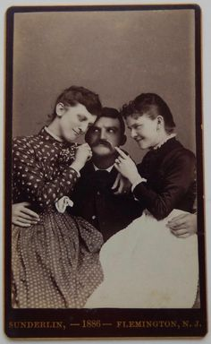 CDV of Two Women Sitting on the lap of a Man with a large mustache.