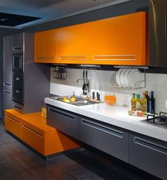 a minimalist kitchen wit graphite grey and orange cabinets looks contrasting and very bold