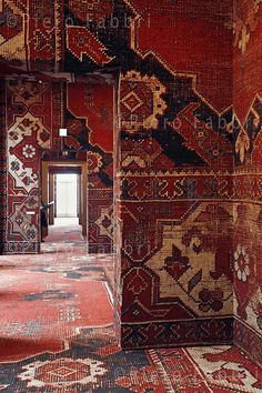 Oxblood tapestry designs on walls and floors. Venice's Palazzo Grassi covered in a carpet by the artist Rudolf Stingel, 2013