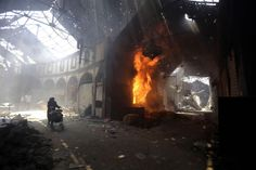 A woman walks past a burning shop in the Maskuf market in the Old City of Homs in Syria on May 12. Syrians streamed back into the ruins of t... #worldnews #Syria