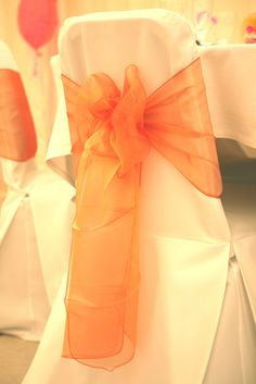 Linen white chair covers with tangerine organsa chair bow.  The finishing touch to a wedding or celebration from www.fuschiadesigns.co.uk.