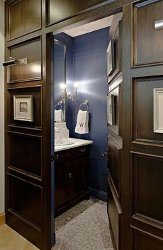 A dark paneled jib door opens to a hidden powder room boasting blue walls lined with a dark stained washstand paired with a honed white marble countertop and backsplash as well as a rectangular polished nickel mirror alongside a mosaic tiled floor.