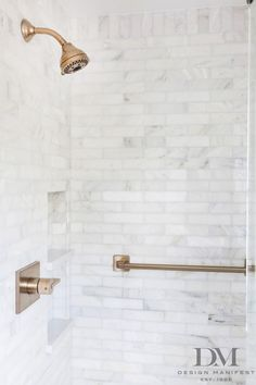 master shower with marble subway tile and brushed bronze fixtures