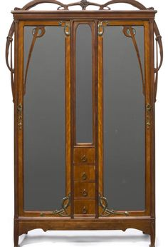 "Léon Bénouville (1860-1903) - Armoire. Carved Walnut with Brass Hardware. France. Circa 1900. 94"" x 58-3/4"" x 19"" (238.8cm x 148.6cm x 48.3cm)."