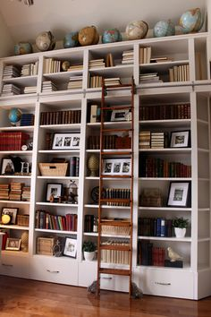 Library Room. Large White Bookshelf with Vintage Desk Globe on High Gloss Wooden…
