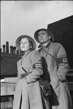 A striking portrait of two civilian firefighters, one male, one female. Both are wearing their Fire Guard armbands, long overcoats and steel helmets. The straps of their gas mask cases can also just be seen. This photograph was probably taken in October 1941.