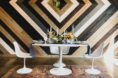 The table in this industrial venue features punchy bright colors, geometric shapes and metallic hints for a mid-century vibe. Via 100 Layer Cake.