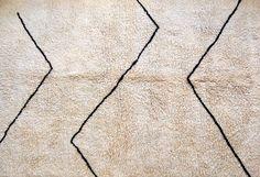 RÉFÉRENCE: B15 DIMENSIONS: 170CM X 255CM COULEURS: BLANCET BRUN FONCÉ  CARACTÉRISTIQUES: 100% LAINE   Les tapis M'RIRTsont des tapis voisins des Beni Ouarain, confectionnés également dans le Moyen Atlas ; leur laine est dense, très douce et soyeuse, nouée densément. Unis ou présentant quelques dessins géométriquesgénéralementépués, les tapis M'Rirt sont une version contemporaine des tapis Beni Ouarain, avec un côté plus lisse et moins ROOARRR (animal NDLR).  Vous souhaitez obtenir…