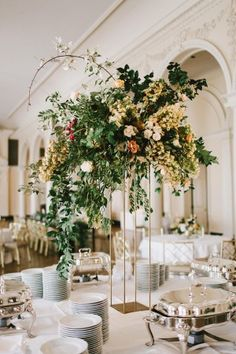 Imagine without the hanging foliage on the left handsome or the single twig at the top poking out. Just to show wild, loose style that is tall and impactful but on a silver elaborate candelabra base.