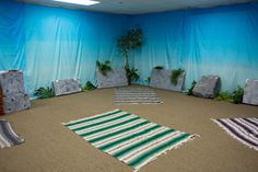 Got a tan carpet? Then you've got sand for Shipwrecked VBS! Add beach towels and scene setters to complete the beachy feel. Explore more decoration ideas at Concordia Supply!