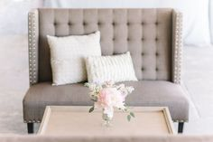 Grey Linen Tufted Sette with Astoria Coffee Table by EventHAUS Rentals | Soft Elegant Wedding at The Historic Rice Mill by Charleston Wedding Planner ELM Events