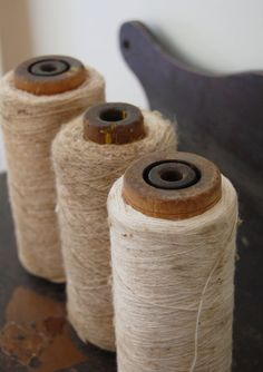 Rustic wood spools with old white yarn
