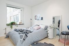 All White Bedroom Bright And Cozy Apartment in Gothenburg Featuring Unique Splashes of Personality