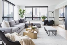 """A pale gray sectional couch elongates the space, and moveable pieces like the chunky, geometric tables make the light-filled room ideal for entertaining. """"The couple can easily have cocktail parties for 12 to 15 in the new layout,"""" says Bednyak. """"This place is the apartment for watching fireworks in the summer."""""""