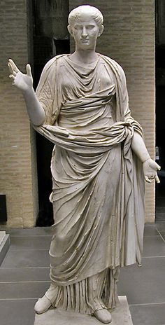 Matrona, a full-size marble statue of an idealized woman, heavily draped and modestly wearing the strapped, floor-length stola of the married Roman woman. Her hairstyle suggests a date in the late 1st century BCE/early 1st century CE. Rome, Vatican museum (Gregoriano Profano).