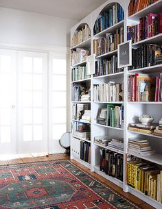 These are the bookshelves in my Williamsburg apartment. I turned my ugly brown Billy bookcases into beautiful built-ins following instructions from Little Green Notebook. (Note: Painting IKEA furniture is not fun. It took many, many coats to turn those brown bookcases white!)
