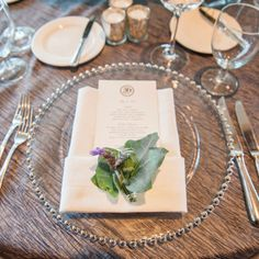 Elegant place settings accented with a bundle of rosemary and thyme | A Day Of Bliss Wedding Photography