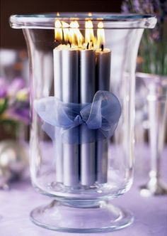 make candles royal blue and/or gold and surround with gypsophilia around the base of hurricane
