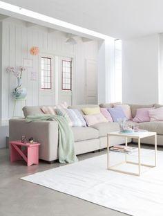 Mooie grote bank en leuk met al die kussens in pasteltinten. Pastel living room.