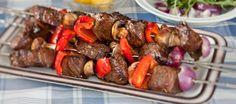 Spiesen voor op de barbecue met gemarineerde stukken biefstuk afgewisseld met champignons, paprika en rode ui