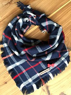 InspirationByTogo Bandanas Are Handmade To Order.  ZODIAC: Bold and masculine. This soft navy plaid flannel bandana with red and white accents in perfect for the boy on the go! Hand fringed designer material finished with a zig zag hem and hand-stitched InspirationByTogo mahogany wood tag. Traditional square Tie on bandana with your choice of color button embellishment. 100% Cotton  *** If you would like the bandana to contain a personalized monogram***  1. Add the bandana of your choice to…