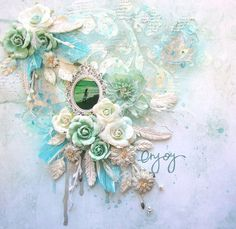 """Enjoy- Scrap Around the World December Challenge Products Papers: 13 Arts Flowers and vines: Prima Feathers and stems: 13 Arts Resin feathers"""" Prima Shimmerz: 4 Leaf clover, Jenny B Blue alpha: Heidi swapp Ranger silver embossing powder Golden white gesso 13 Arts Acrylic primer Metal frame: Prima script stamp: Glitz design Cheese cloth"""