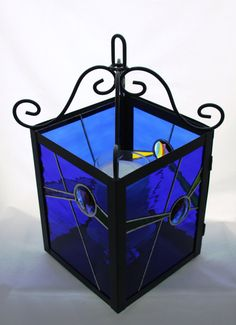 A very modern cobalt blue lantern, with angles of bright yellow, green, and purple against a wavy waterglass of blue...sparkles and reflects. Love this!