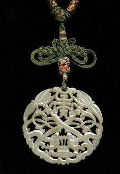 """PENDANT - Finely carved and reticulated Chinese White Jade round Pendant with original woven metallic thread and silk cord. Attached 1898 acquisition note. 2 1/4"""" diam., 1/8"""" thick; 17"""" long."""