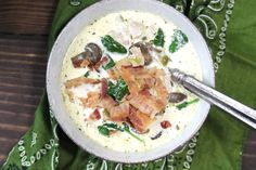chicken, bacon, mushrooms, spinach, all mixed together win broth with melted butter heavy whipping cream and thyme in a white bowl and silver spoon on top of a green bandana.