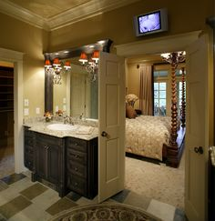 Large walk-in bathroom with double sinks and tiled floor with open space and a security screen above. Remodeled bathroom leads right into the master bedroom. French doors and granite countertops give the bathroom that elegant flair.