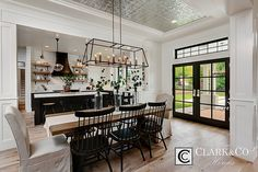 """Clark & Co Homes - 2016 Spring Parade Home """"The Heartland"""". Modern Farmhouse. www.clarkandcohomes.com Built-in cabinetry; White Oak Beams; Painted brick fireplace; Shaw White Oak engineered wood flooring; White Dove by Benjamin Moore; Black Magic. Shiplap paneling. Dining Room. French doors. Floating shelves custom wood Kitchen hood. Tin ceiling."""