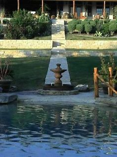 Poolside fountain with stone retaining walls and pathway.