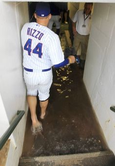 Anthony Rizzo removes his spikes and socks to walk down the flooded walkway to the Cubs' clubhouse