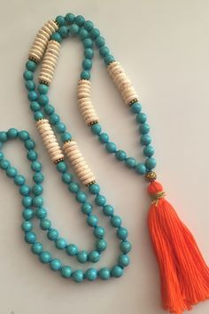 Blending white and turquoise colored howlite beads with the bright orange tassel make it a great, unique piece to wear! It is one-of-a-kind, hand-knotted necklace with round and disc shaped howlite beads and gold tone accent beads.