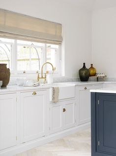 Beautiful modern farmhouse style kitchen with apron front farm sink, dark blue island, and brass faucet. Design by Devol.