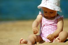 A baby in their first swimsuit is so totally adorable, especially baby girls. Love this photo; barely able to sit up on her own, slathered in sunscreen, dressed in pink adorableness, and working on her first sand castle.