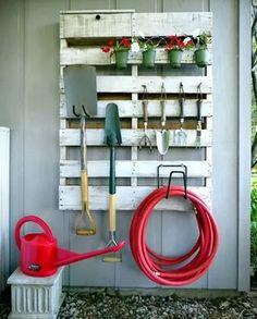 Een pallet aan de muur is ideaal voor het opbergen van tuingereedschappen!