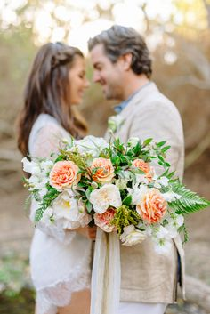 The bride carried a lush garden bouquet of peach and ivory roses, white sweet peas, and ferns. The handle was wrapped with streamer ribbons of cream silk and ivory lace.  Photos and Styling by Mike Arick Photography