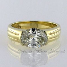 Centre stone is a 2.964ct N/SI3 oval cut diamond placed on it's side in a half tube setting, 18k yellow gold wide band with grooves