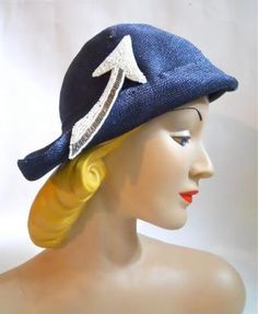 1930s blue sisal asymetrical hat with white and silver beaded arrow on right side. Label: Styled by Janet.  Via Dorothea's Closet Vintage.