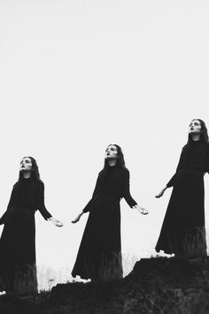Girls donning black dresses with their palms turned toward the sky, singing hallelujah.