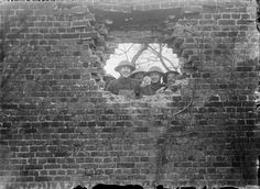 British soldiers looking out a shell hole in the wall of a house in Hebuterne/1916