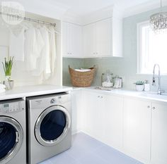 Laundry room with hanging areas, a sink, counter space, cabinet storage and a glam chandelier.