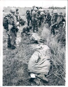 Chaplain kneels as he prays over the covered bodies of two U.S. Marines killed by Viet Cong fire Dec. 1st. The Marines were killed during a patrol of Operation Meade River, 15 miles south of Da Nanag. UPI PHOTO 12/6/68